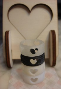 Heart Rings stacked up infront of a plywood photoframe from Ponoko